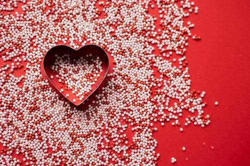 Top view of heart shaped form for baking among sweet sugar sprinkles scattered on red background as symbol of Saint Valentines Day