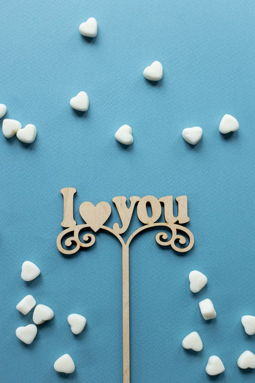 Top view composition of topper in form of declaration of love among heart shaped sugar sprinkles on blue background