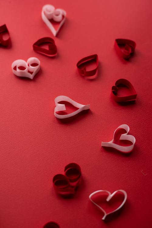Small paper hearts for Valentines Day on red background