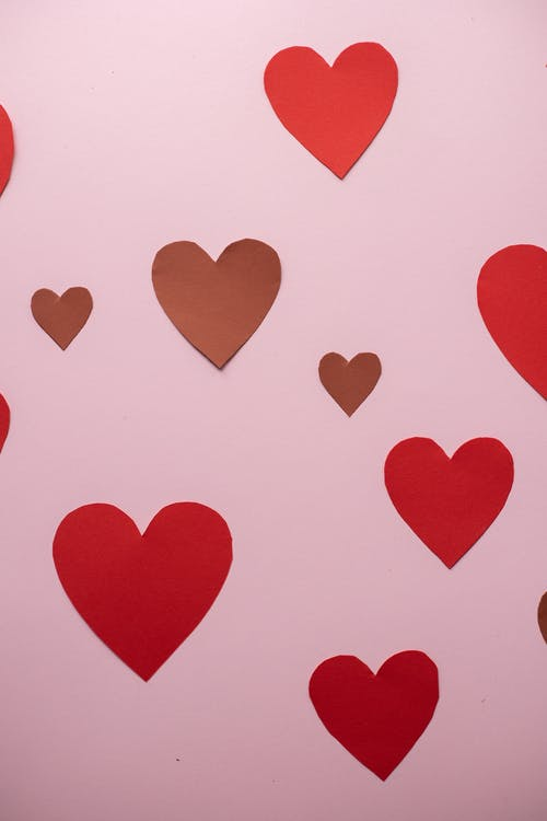 Paper hearts glued to pink wall