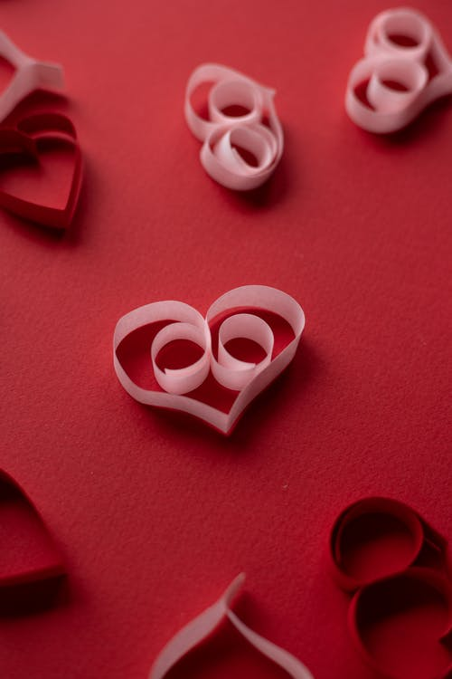 Paper hearts scattered on red surface
