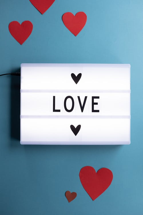 Paper hearts around Love inscription on light box