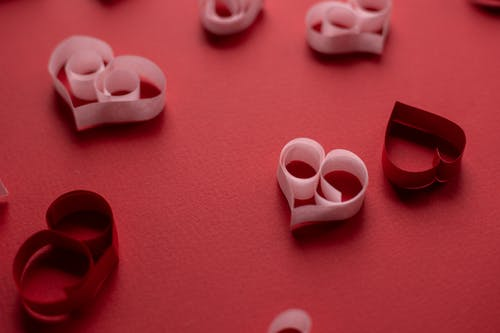 From above of small cutout heart shaped decorations for celebrating romantic event Saint Valentines Day