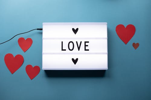 Composition of light box with Love word and glued paper hearts for Saint Valentine concept