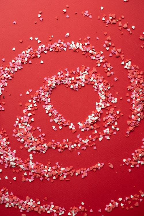 Top view of small confectionery topping scattered on surface and forming heart shape on bright background during saint valentines day celebration