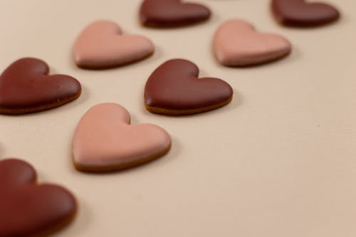 From above of red and pink heart shaped cookies with frosting arranged in rows on beige background during valentines day