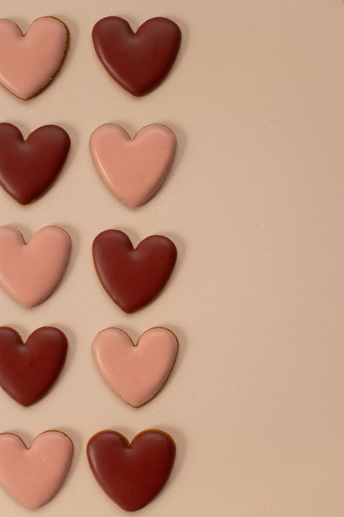 Top view of tasty pink and red heart shaped cookies with glaze arranged in rows on beige background during valentines day celebration