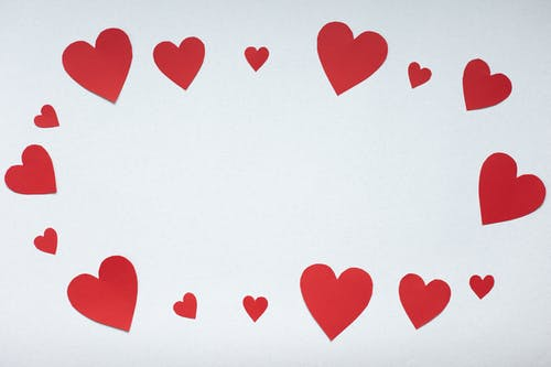 Top view paper cutout of different sizes red paper hearts forming oval placed on white background during valentines day celebration concept