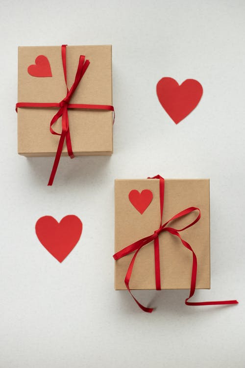 Top view of cardboard boxes tied with ribbons placed on white background with paper red hearts during saint valentines day