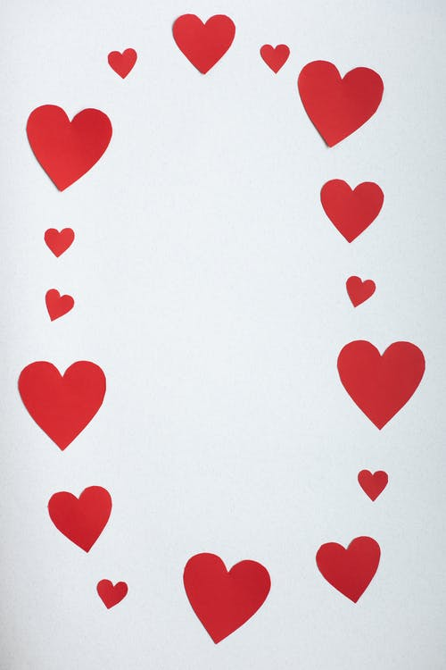 Top view paper cutout of different red hearts arranged in shape of oval on white background during saint valentine day