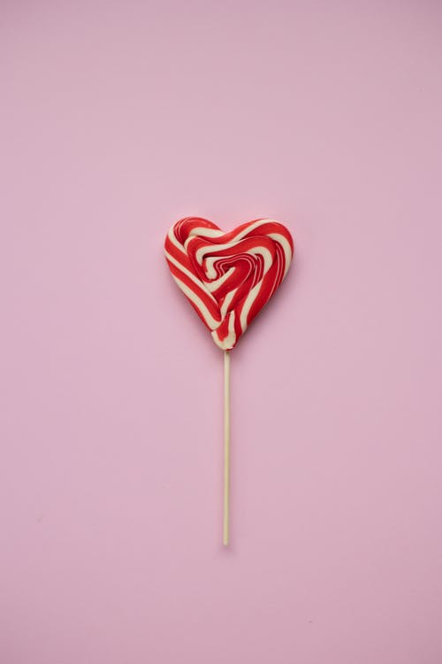 Top view of tasty red and white heart shaped lollipop  on wooden stick placed on pink background during holiday celebration