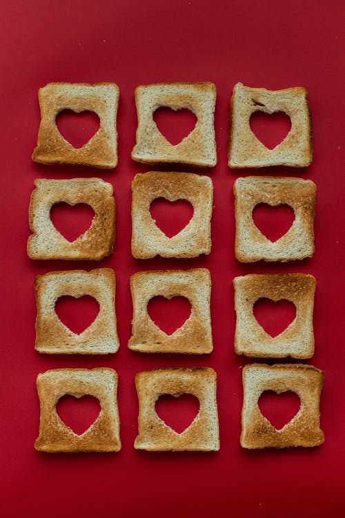 Top view of composition of slices of toasted bread with cut out hearts against red background