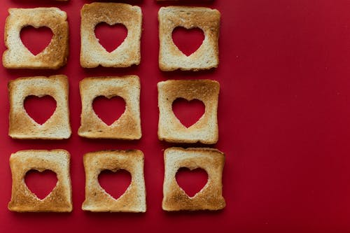 Composition of creative slices of toasted bread against red background