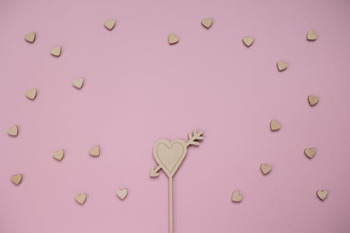 From above of composition of wooden heart with arrow surrounded by small wooden hearts against pink background