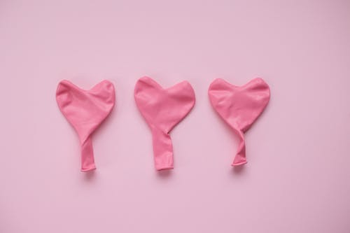 Top view of pink deflated balloons in form of hearts placed on pink background in studio