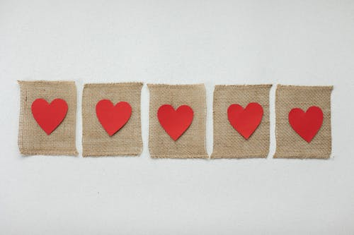 From above of handmade burlap pieces of fabric with bright red hearts placed on white background