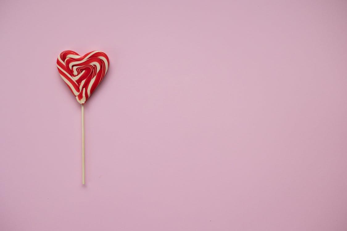 Sweet lollipop in form of heart on pink background