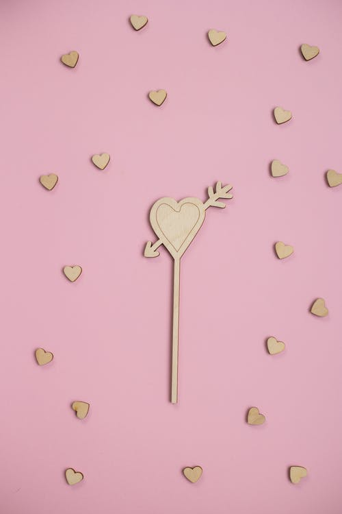 Top view of composition of creative wooden hearts placed on pink background in studio