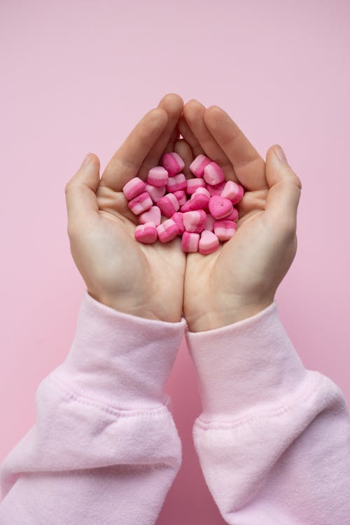 Person showing small candies in shape of hearts in hands