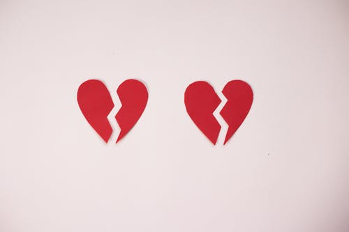 Broken paper hearts on white background