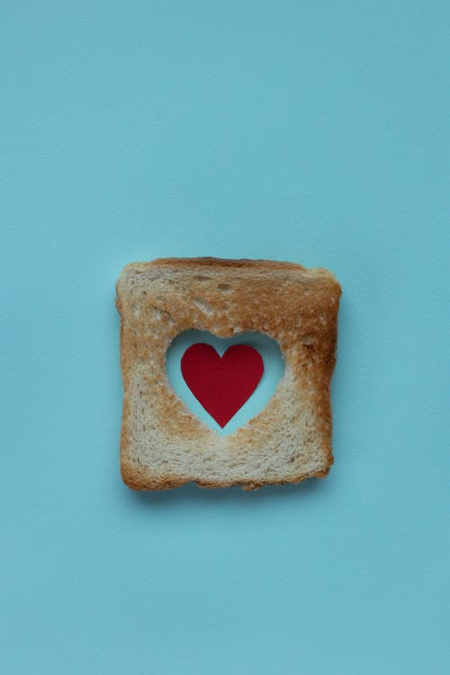 From above of piece of white bread with red paper heart on blue background