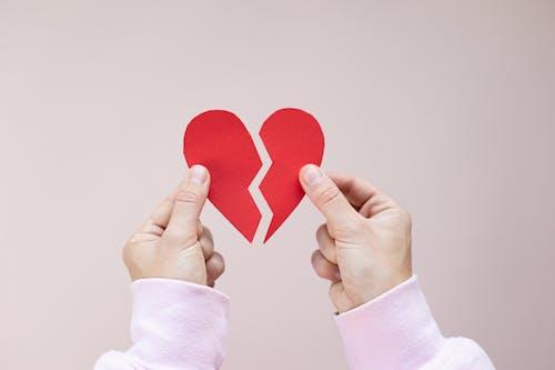 Crop person showing broken paper heart