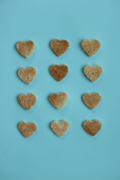 From above of crusty edible hearts from white bread on bright blue background