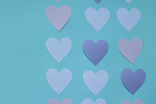 From above of paper hearts with gentle colors on blue surface in studio