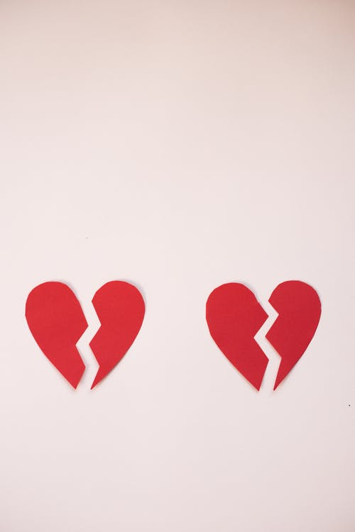 From above of cut parts of red broken hearts on light white background