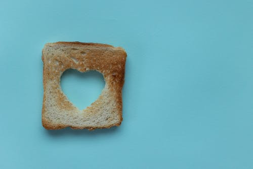 Top view of piece of white bread with cut heart on blue background