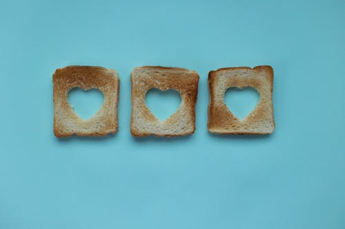 Top view of crusty pieces from toast bread with cut hearts on blue background