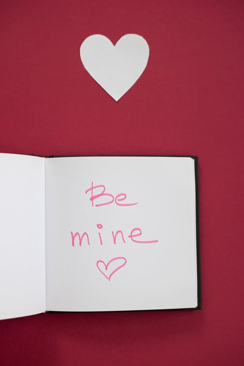 Opened notebook and cutout paper heart