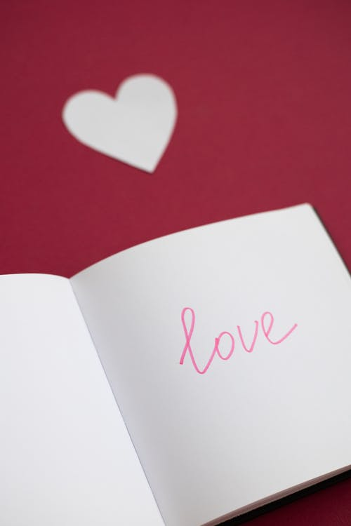 High angle of opened notebook with word and cutout paper heart on red background