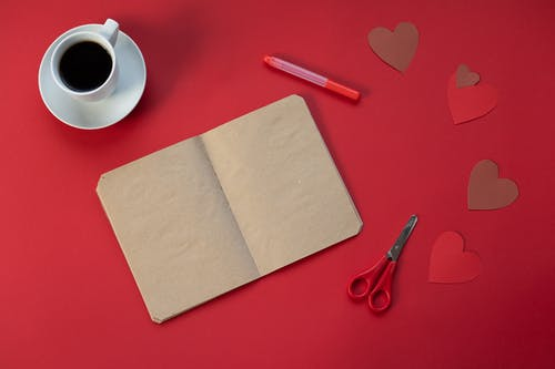 Top view of craft papers near scissors and cup of hot coffee on red background