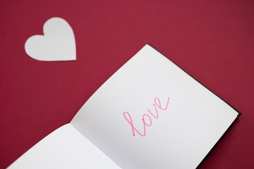 From above of love inscription on paper in front of cutout paper heart on red background