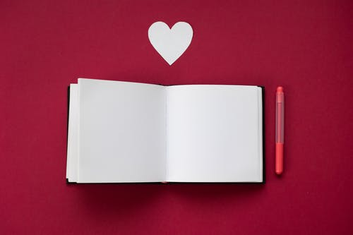 Empty notebook near marker and heart