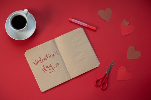 Paper hearts and notebook near coffee