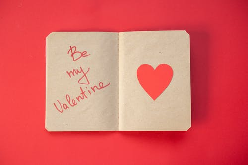 Top view of romantic phrase written on craft paper of notepad with heart placed on red background during Saint Valentines day