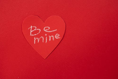 Top view of Be Mine phrase written on heart shaped piece of paper placed on table during Saint Valentines day celebration