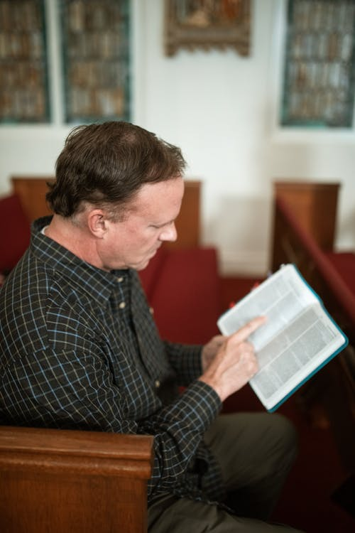 Side view of concentrated senior male in casual clothes reading holy book while sitting on bench in church