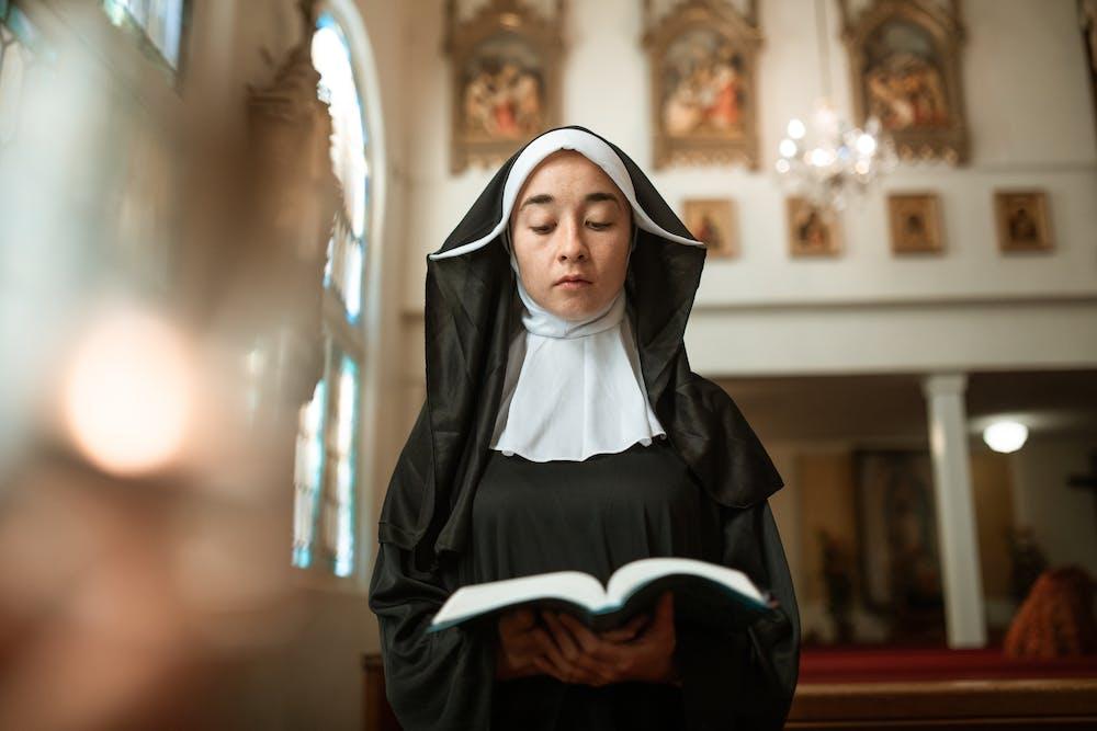 A nun reading the bible. | Photo: Pexels
