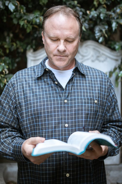 Man in Blue and White Checkered Dress Shirt Reading Book