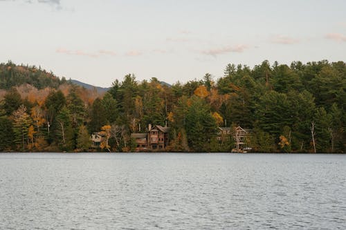 Traditional cottages in autumn forest on lake shore