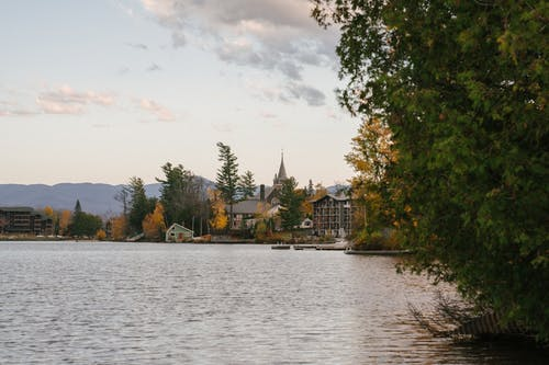 Peaceful lake with residential cottages and lush trees on shore in autumn