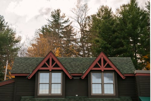 Facade of aged residential cottage located in autumn forest against cloudy sky