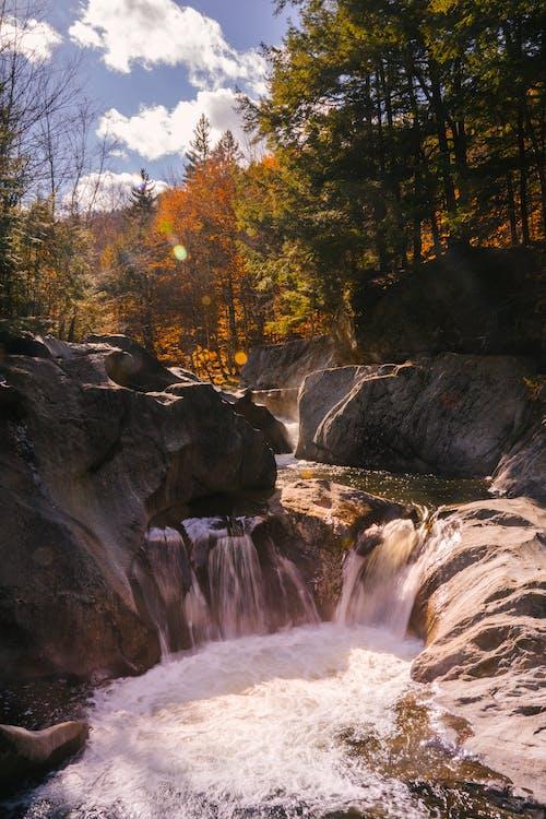 Waterfall flowing among big rocks in autumn woods
