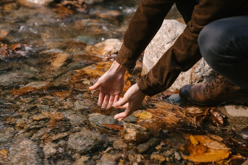 Side view of crop anonymous male in outerwear washing hands in water of lake with transparent water