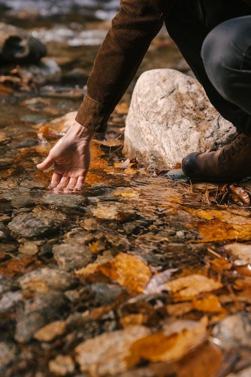 Man on hunkers on stony coast of lake