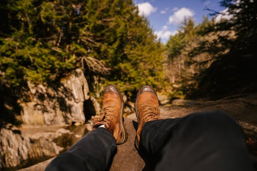 Crop legs of anonymous traveler lying on rocky cliff in green woods in sunny day