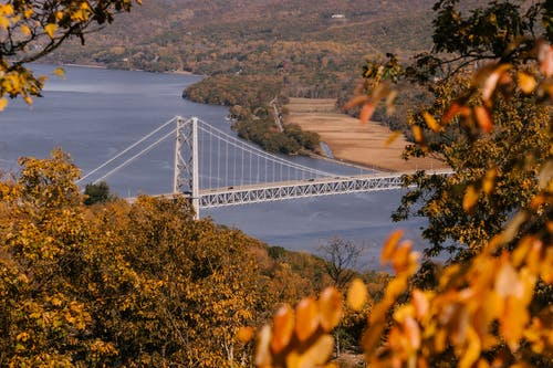 Suspension bridge over calm river flowing through hilly terrain covered with lush autumn trees